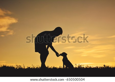 Silhouette boy playing with little dog on the sky sunset color of vintage tone #650500504