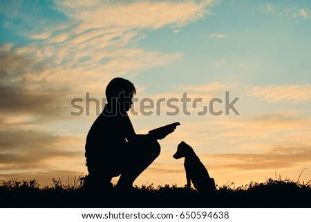 Silhouette boy reading a book with little dog on the sky sunset color of vintage tone #650594638