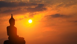 Silhouette Buddha on sunset background shining from behind