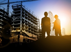 silhouette Businessman engineer looking blueprint in a building site over Blurred construction site film grain progress and potential personal and career growth concepts.