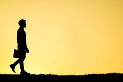 Silhouette businessman, holding briefcase, walking on grass field, silhouetted against warm tone sunshine in the morning light with tranquil scene.