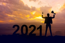 Silhouette businessman holding up a gold trophy cup as a winner in a competition and  2021 years with sunset background,Success new year concept.
