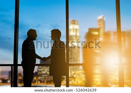 Silhouette businessmen shake hands finishing a deal between businesses Success of the joint venture business growth progress and potential concept over blurred employees the city night and flare light #526042639