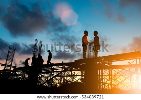Silhouette businessmen shake hands finishing a deal between Organization Success joint venture growth progress and potential over blurred employees at Construction Site with flare light #534039721