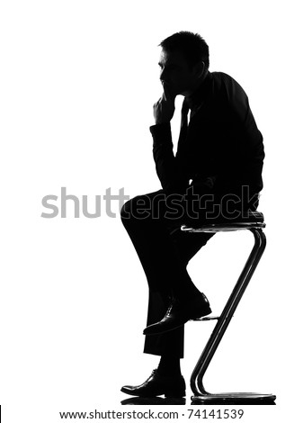 silhouette caucasian business man thinking pensive sititting on foot stool full length on studio isolated white background