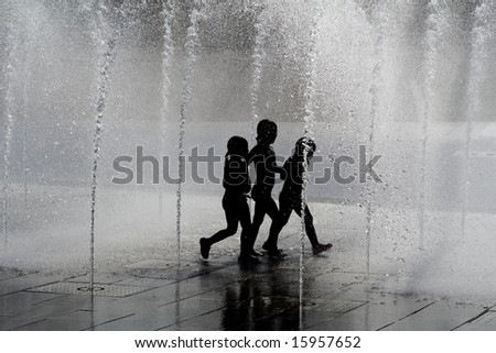 silhouette children playing in water fountains