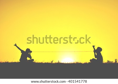 Silhouette children playing string phone at sky sunset