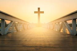 silhouette christian cross at railhead wooden bridge and orange sky with lighting,religion concept