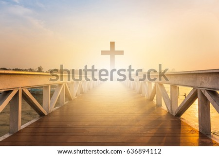 Silhouette christian cross at railhead wooden bridge and orange sky with lighting,religion concept.