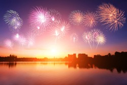 Silhouette city urban communities with soft focus sunset and colorful fireworks background. Blurred blue purple sky peaceful glow bright during twilight. Outdoor water open view. Landscape celebration