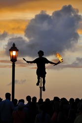 Silhouette close up of a performer on a unicycle juggling multiple batons with fire in the evening in Key West, Florida, USA with a small crowd against setting sun