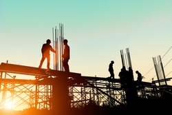 Silhouette construction industry engineer standing orders for worker  team to work safety on high ground over blurred background sunset pastel