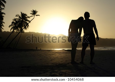 silhouette couple on tropical beach by sunset
