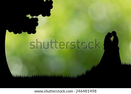 Silhouette couple stand on the grass green background