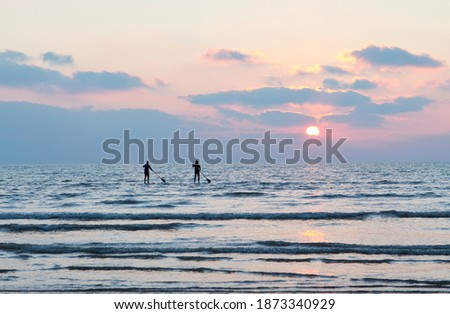 Silhouette couple standing on paddleboards in the ocean at sunset Stock photo ©