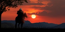 silhouette cowboy horseback riding transportation at sunset time with mountaind and sun sky background.