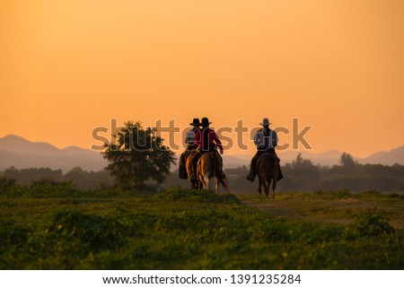 Silhouette Cowboy riding a horse  under beautiful sunset #1391235284