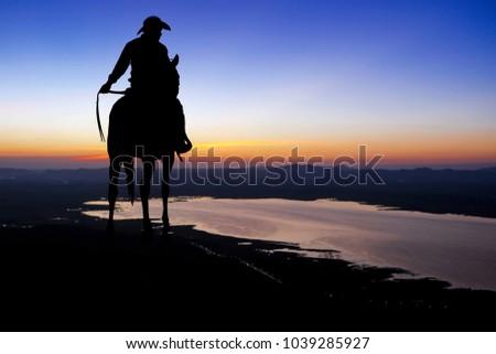 Silhouette cowboys riding horse.