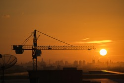 Silhouette Crane in building construction site on Sunset Background