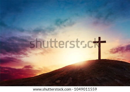 Silhouette cross on Calvary mountain sunset background. Easter concept #1049011559