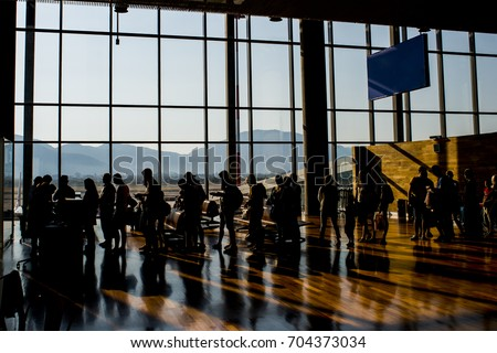 Silhouette crowd people waiting for airplane in airport terminal with mountain background