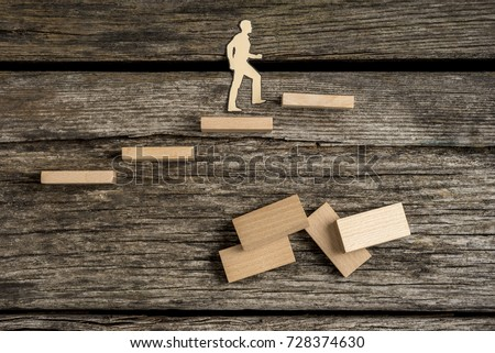 Silhouette cutouts of a man walking up wooden steps with dominos over old rough wooden table surface. #728374630