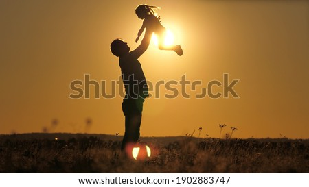 Silhouette dad throws happy little daughter into the sunset sky. Father's day. The child wants to fly above the ground. A parent with a child plays at dawn. Family and childhood concept. Kid jumps on