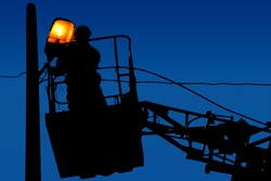 Silhouette electrical engineer is repairing on a light pole on the blue sky background