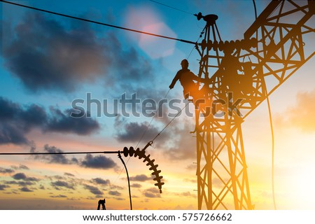 Silhouette electrician work installation of high voltage in high voltage stations safely and systematically over blurred natural background.