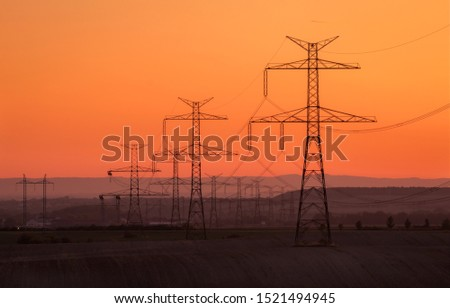 Silhouette electricity pole, electricity pylons technology on sunset time background, Ceske Stredohori, Czechia
