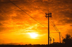 Silhouette electricity post with beautiful sunset background.