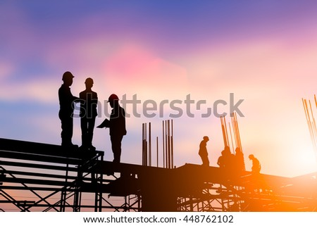 Silhouette engineer construction industry stand to talk about the work of the construction team that work just as construction planned over blurred pastel background sunset . Heavy industry concept.