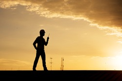Silhouette engineer hold radio for order construction crews to work safety with telecom tower.
