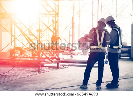 Silhouette engineer in safety protective equipment standing orders for construction crews to work at building construction site. It's a key successfully for business, successful concept