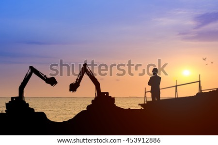 Silhouette engineer looking construction worker  with sunset background in a building site.Over Blurred construction worker on construction site nearly sea beach with sunset background bit coin