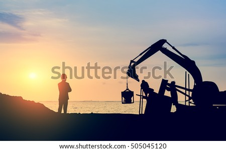 Silhouette engineer looking construction worker  with sunset background in a building site.Over Blurred construction worker on construction site nearly sea beach with sunset background bitcoin
