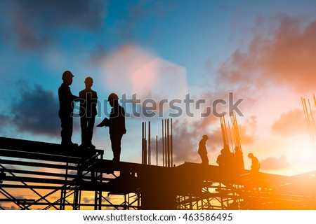 Silhouette engineer standing orders for construction and discuss the contract with the sub contractors Heavy industry and safety at work over blurred  background sunset pastel