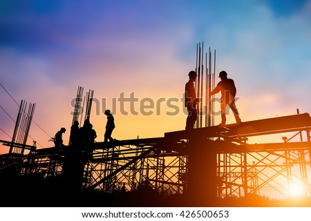 Silhouette engineer standing orders for construction crews to work on high ground  heavy industry and safety concept over blurred natural background sunset pastel #426500653