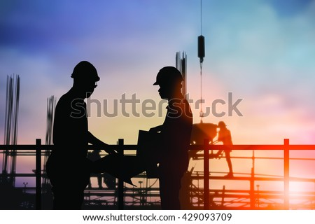 Silhouette engineer standing orders for construction crews to work safely on high ground over blurred construction workers natural background sunset pastel. heavy industry and safety at work concept.