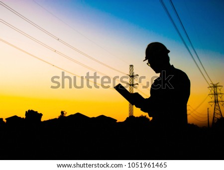 Silhouette engineer working at construcktion on twilight background,Silhouette electrical engineer picture