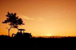 Silhouette Farmers drive tractors The fields in the morning