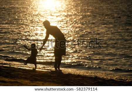 silhouette father and son stand on the beach in sunset time and reflex in ocean