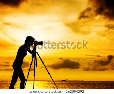Silhouette female photographer at sunset