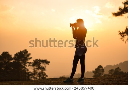 Silhouette female photographer taking a picture with the sun behind