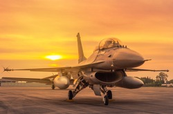 Silhouette fighter jet military aircrafts parked on runway in sunset twilight time