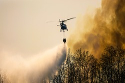 Silhouette firefigthing helicopter dropping water on forest fire