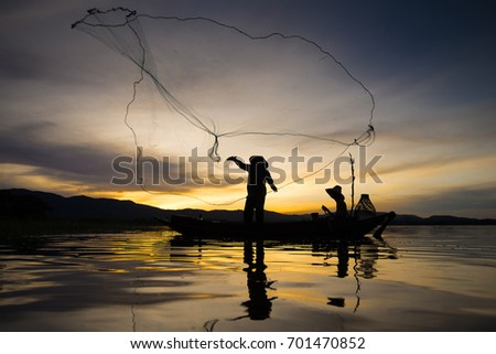 Silhouette Fisherman and son are fishing net in the river. Occupation of fisherman, Thailand #701470852