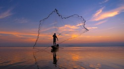 Silhouette Fisherman fishing nets on the boat. Silhouette of fishermen using coop-like trap catching fish in lake with beautiful scenery of nature morning sunrise.