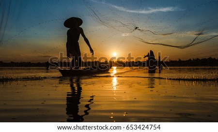 Silhouette Fisherman Fishing Nets on the boat.Thailand #653424754