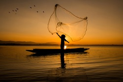 Silhouette fisherman throwing net casting fish in early morning with wooden boat with a flock of birds, Fisherman life style